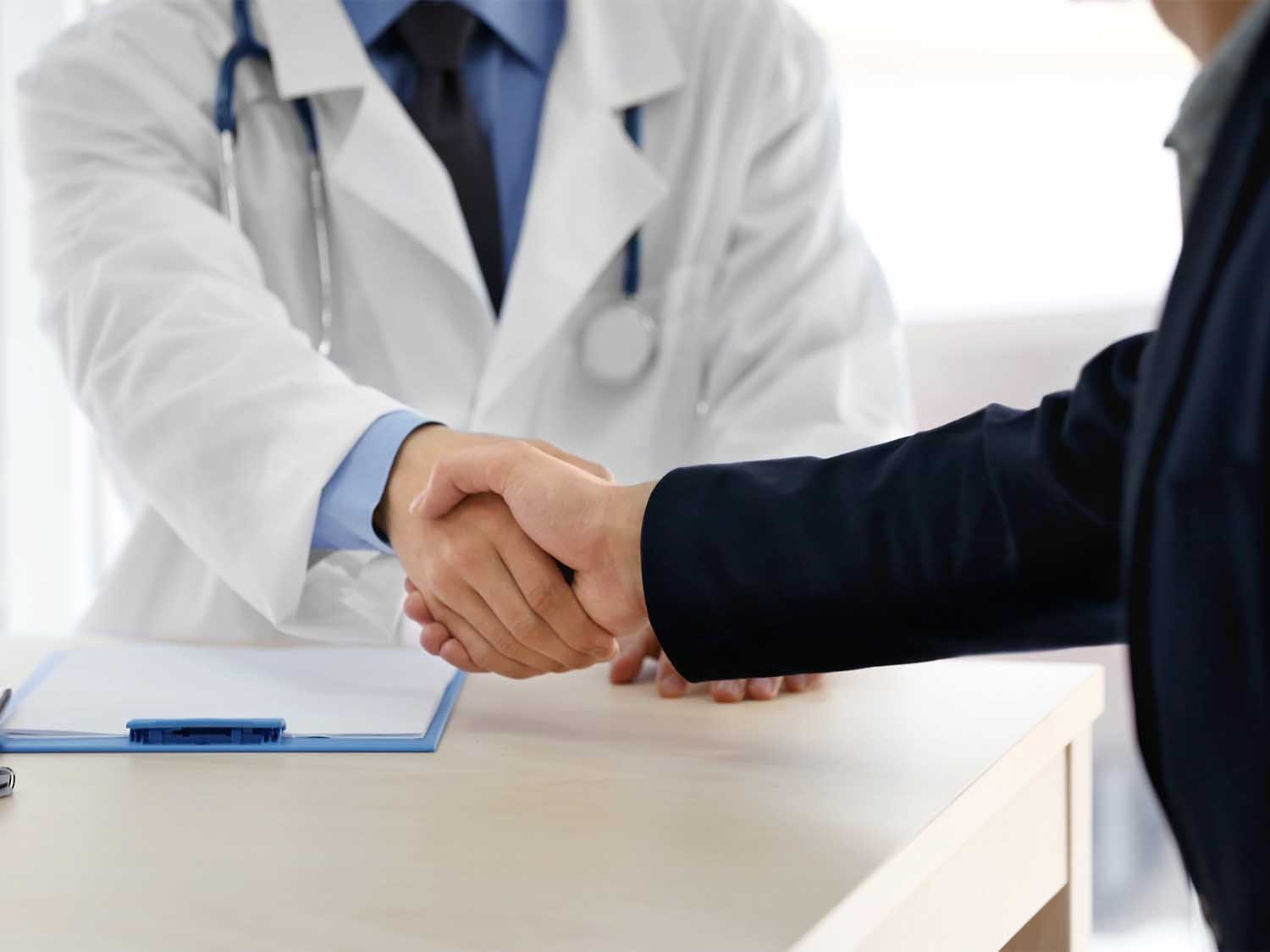 A Medical Malpractice Insurance Broker And Doctor Shaking Hands