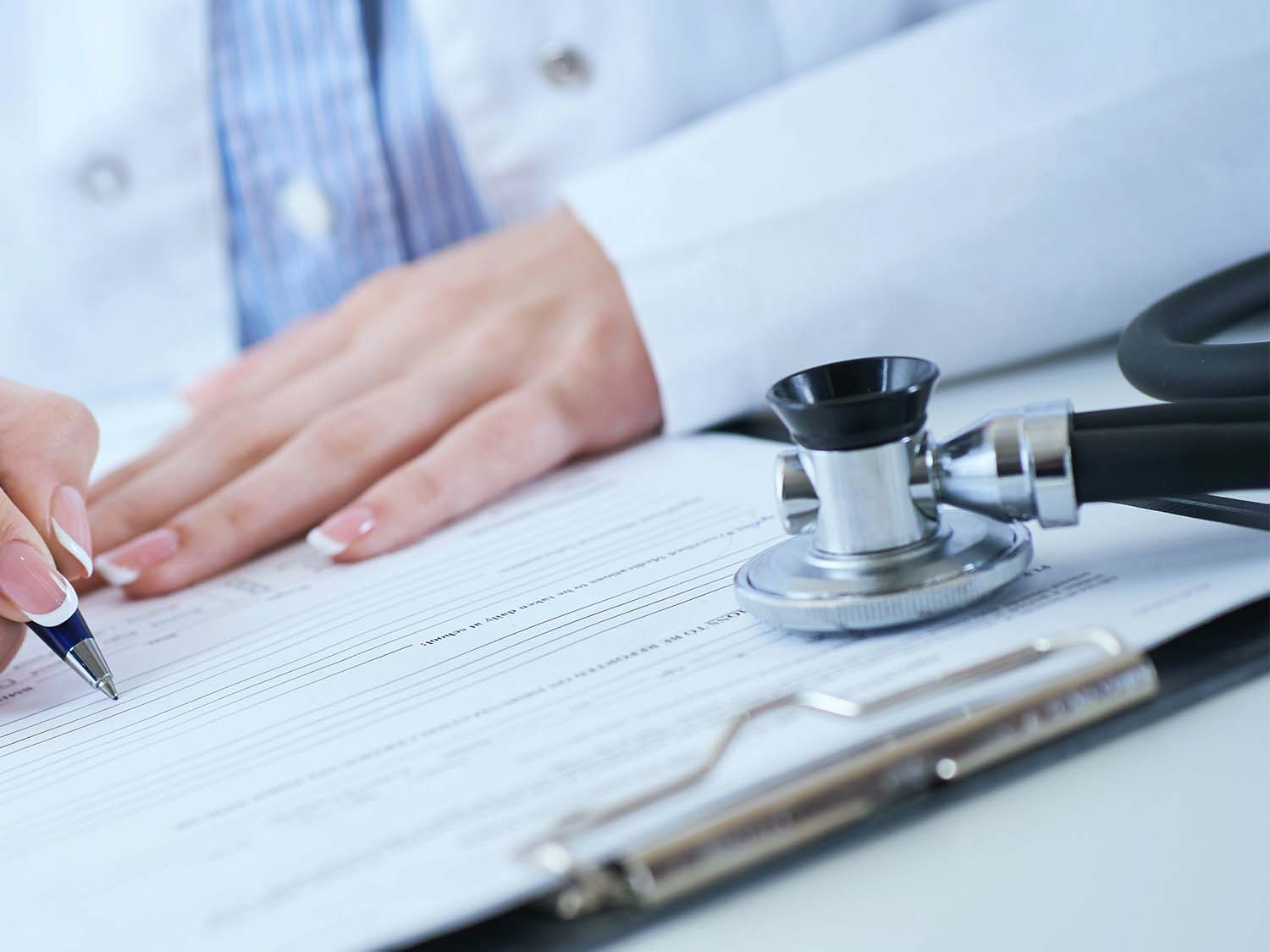 A Doctor Completing Medical Malpractice Insurance Quote Paperwork