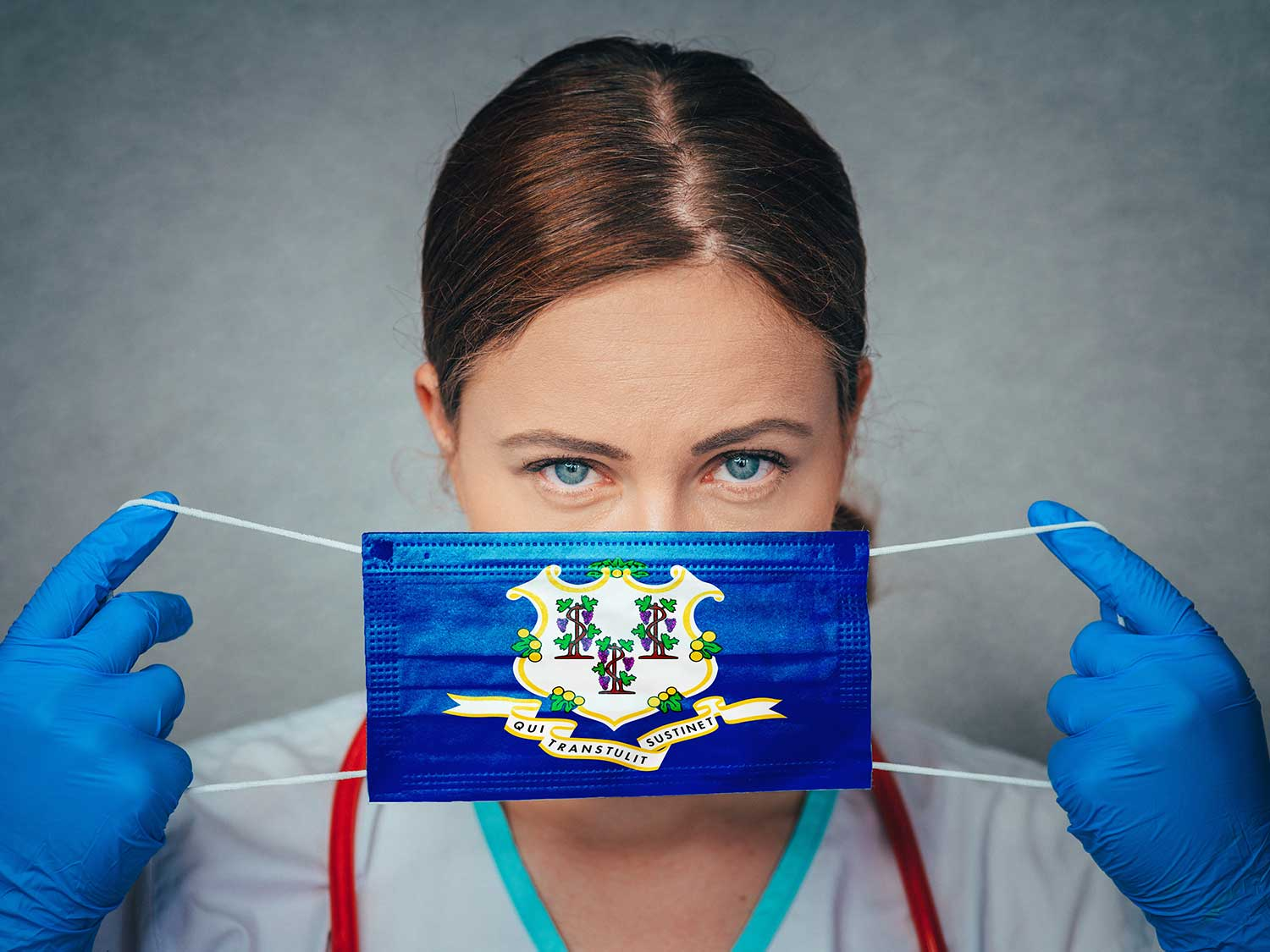 Surgeon With Medical Liability Insurance Placing A Mask With The Connecticut State Flag Over Her Face