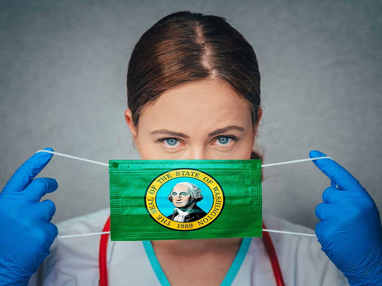 Physician Holding A Mask Over Her Face With The Washington Flag On It