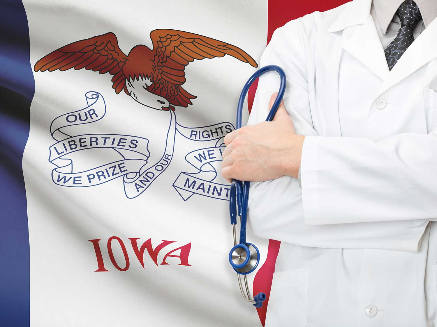 Doctor With Liability Insuance Standing In Front Of Iowa State Flag With Arms Folded