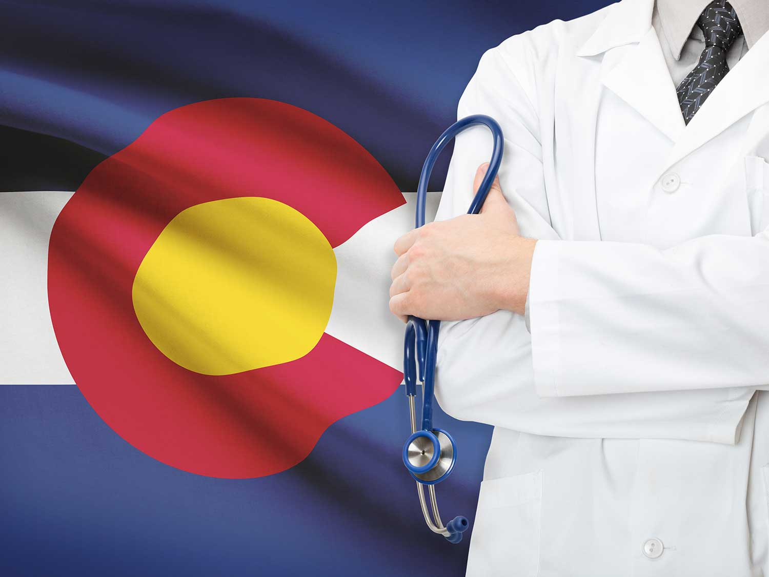 Doctor With Medical Malpractice Insurance Standing In Front Of Colorado State Flag Holding Stethoscope