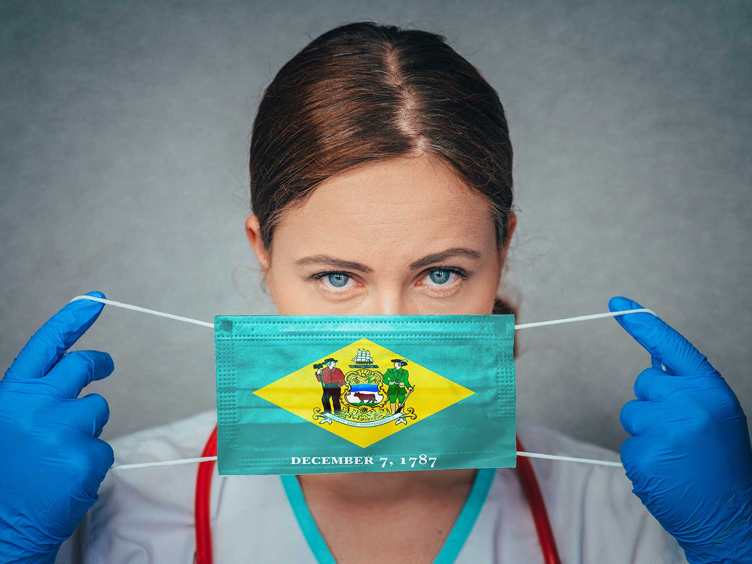 Female Doctor With Medical Malpractice Insurance Holding Mask With Delaware State Flag Printed On It