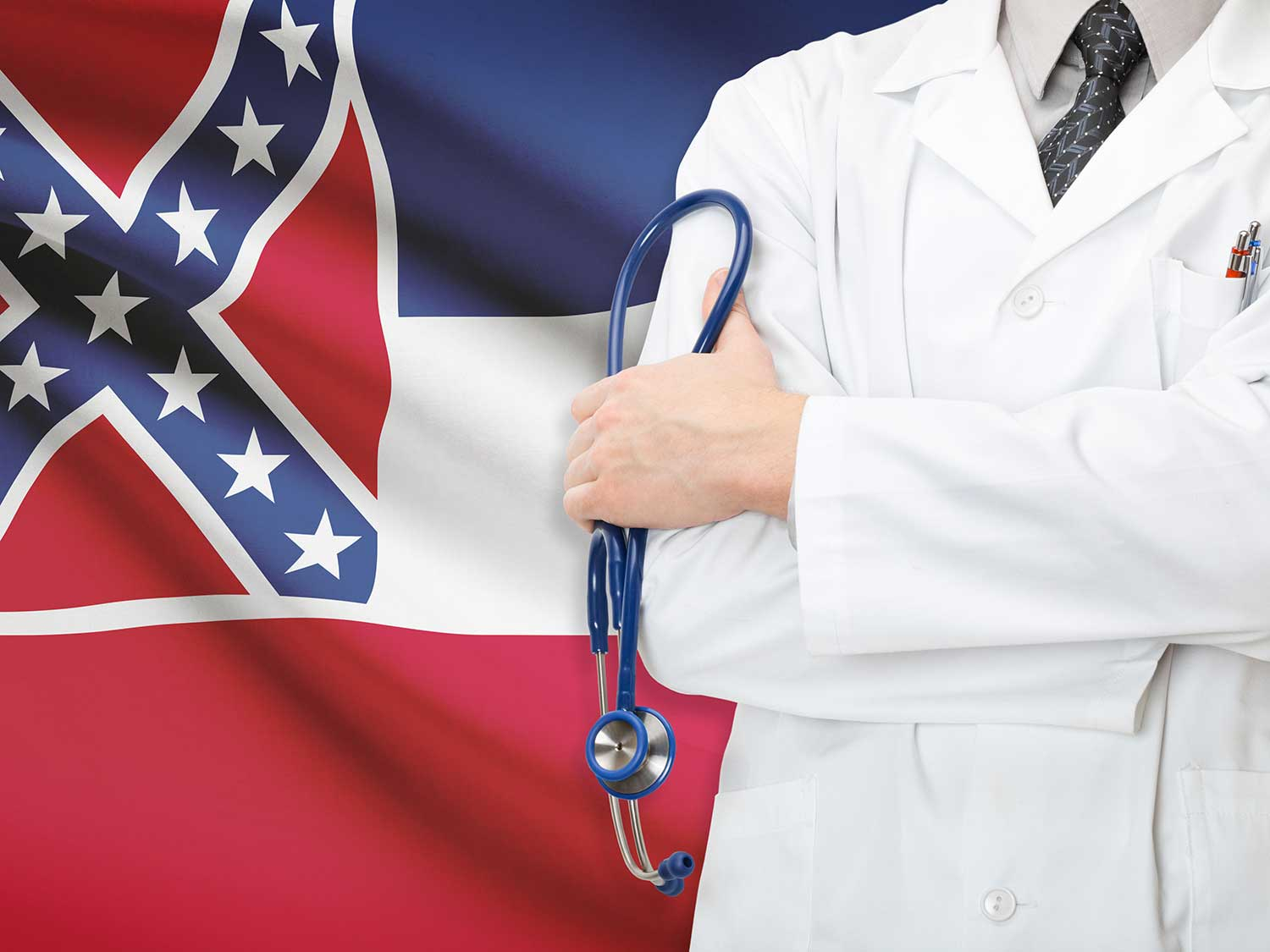 A male Doctor With Medical Malpractice Insurance Folding His Arms In Front Of The Now Retired Mississippi State Flag